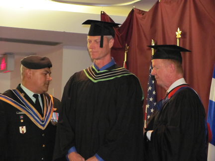 photo of Huckabee and Commandant Plourde hooding a PA Master's degree candidate.