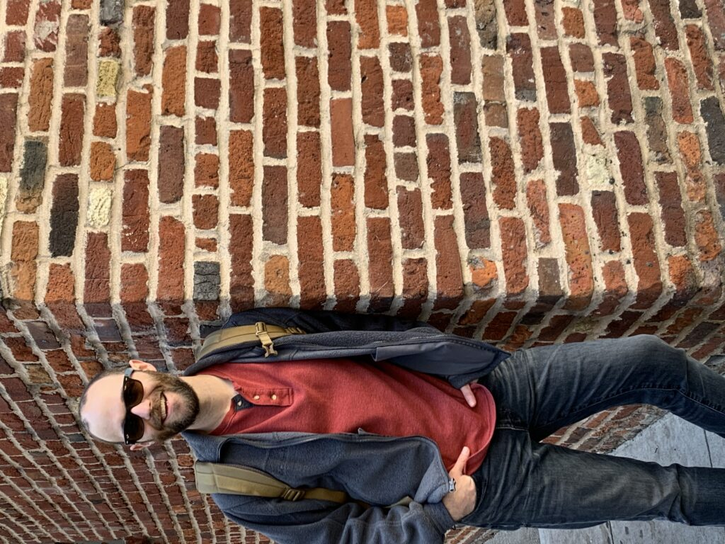 Image of ID fellow Dr. Bryan Walker wearing a red shirt and blue jacket and dark blue jeans and sunglasses leaning against a brick wall