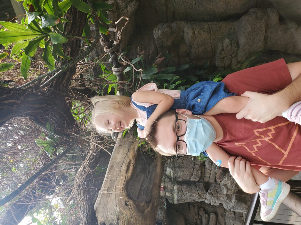 Jeremy wearing a mask with his daughter on his shoulders laughing underneath a tree