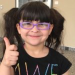 young girl with glasses giving thumbs up