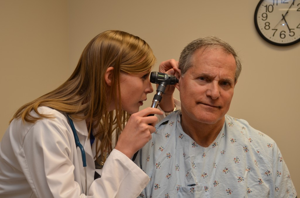 Standardized patient Gary Javitch gives a masterful performance while being examined by physician assistant student Megan Punt.