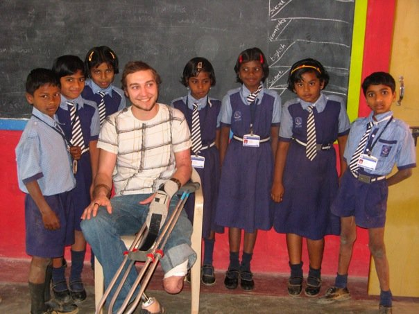 Caleb Baber surrounded by kids on a mission trip to India. He hadn't yet received his second prosthetic leg.