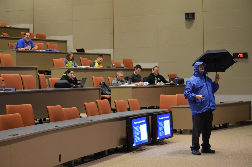 Dr. Vandenberg donned a rain slicker and wielded an umbrella for a lecture on incontinence.