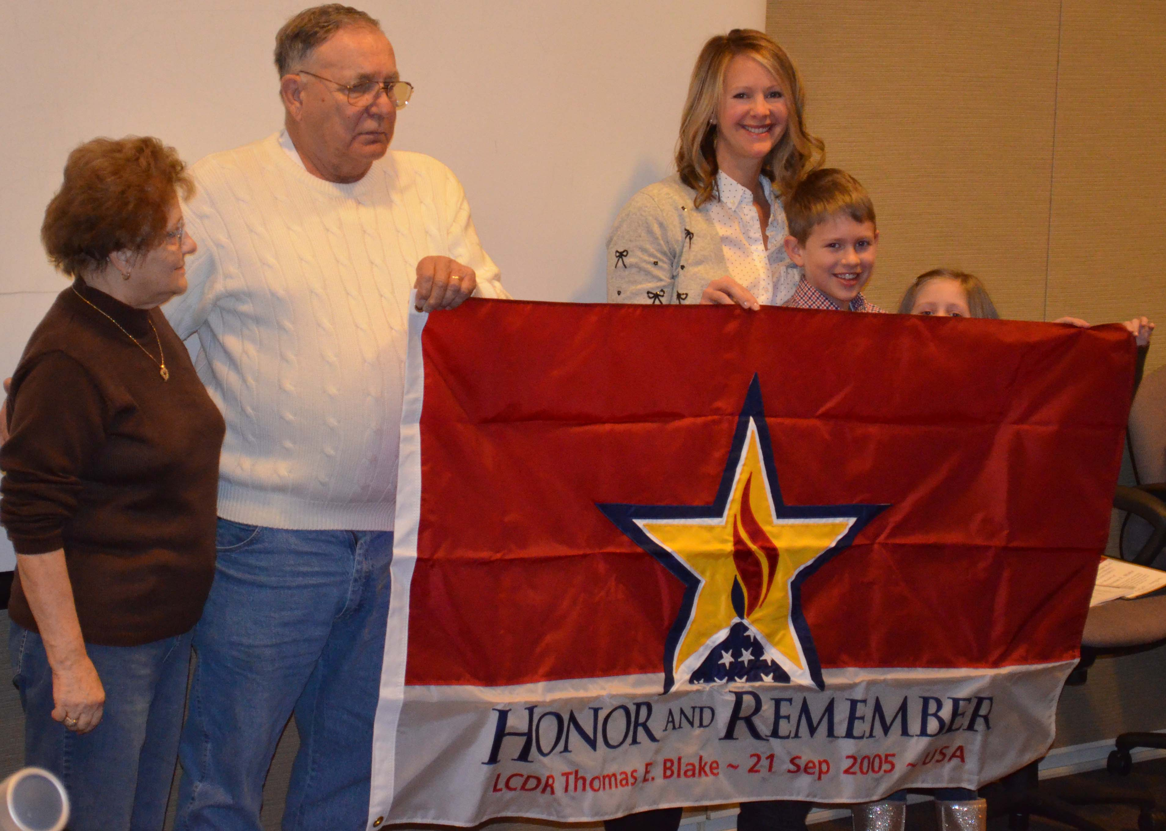 UNMC nursing student Jessica Blake, third from left, holds a flag that honors her husband, Thomas, a Navy pilot who died in the line of duty. With her are her husband's parents, Carole and Tom, and her children, Tommy and Lily.