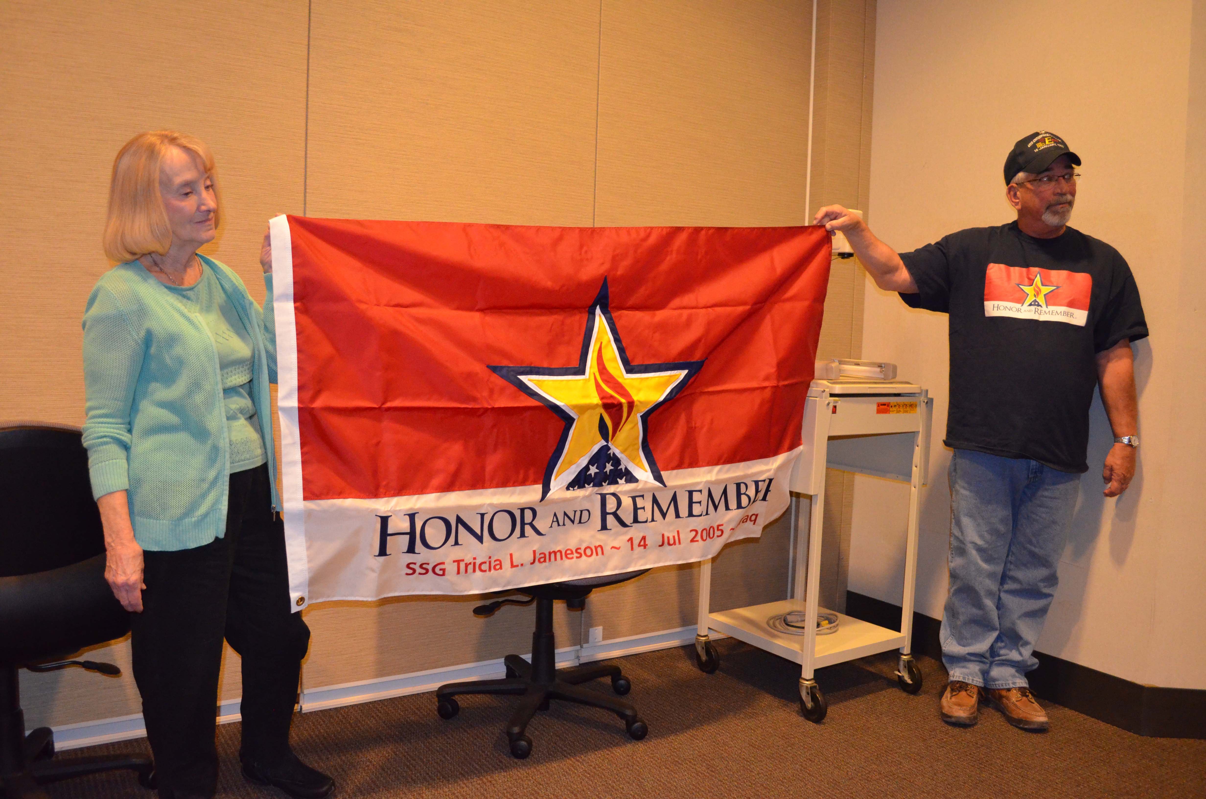 Tricia's mom, Pat, displays the flag presented her by UNMC nursing students with volunteer Cliff Leach.